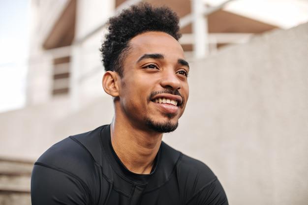 Portrait en gros plan d'un homme à la peau foncée brune bouclée en t-shirt à manches longues souriant sincèrement et posant à l'extérieur