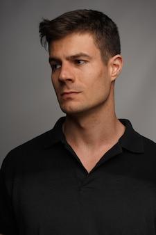 Portrait en gros plan d'un homme séduisant dans un t-shirt noir contre un mur gris