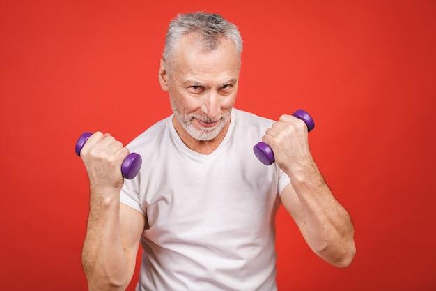 Portrait de gros plan d'un homme senior exerçant avec des haltères.