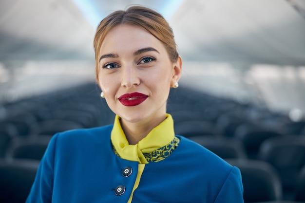Portrait en gros plan d'une hôtesse de l'air souriante et heureuse en uniforme bleu et jaune regardant l'appareil photo à bord d'un avion moderne