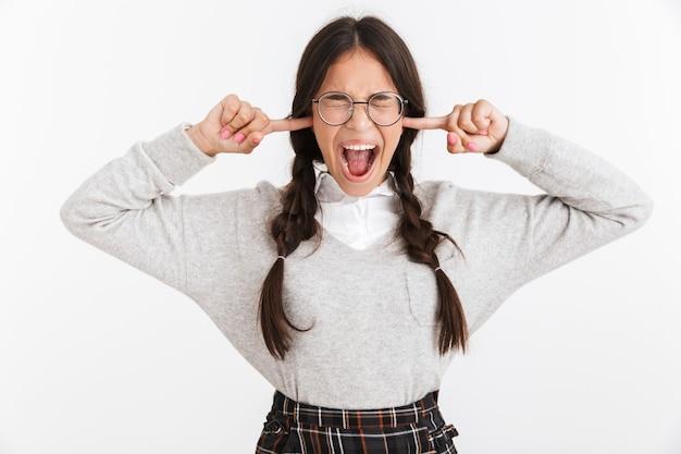 Portrait en gros plan d'une jeune adolescente portant des lunettes et un uniforme scolaire criant tout en se bouchant les oreilles avec des doigts isolés sur un mur blanc