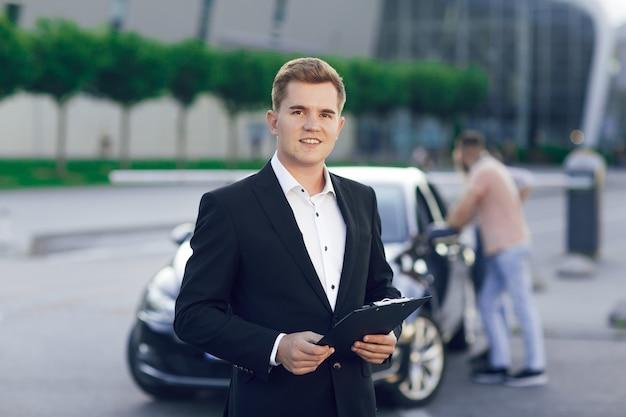 Portrait en gros plan d'un jeune concessionnaire automobile dans un costume d'affaires. derrière lui, un jeune couple, un homme et une femme inspectent une nouvelle voiture. achat de machines, essai routier.