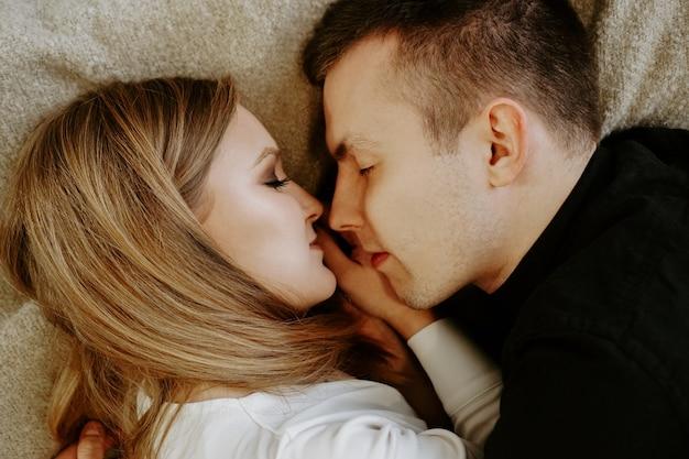 Portrait de gros plan d'un jeune couple au lit à la maison