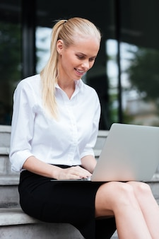 Portrait en gros plan d'une jeune femme d'affaires assise dans les escaliers et travaillant sur un ordinateur portable