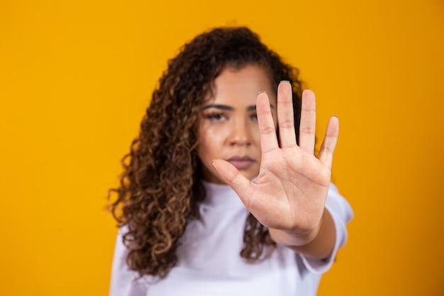 Portrait en gros plan d'une jeune femme africaine sérieuse montrant un geste d'arrêt avec sa paume isolée