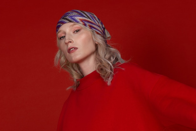 Portrait en gros plan d'une jeune femme blonde avec un foulard sur le fond rouge