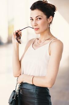 Portrait de gros plan de jeune femme brune élégante en soie crème