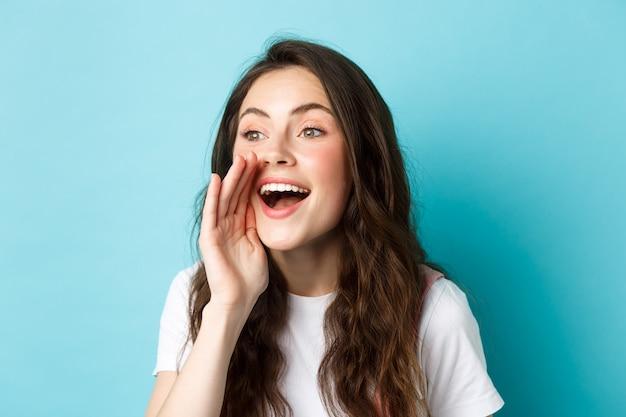 Portrait en gros plan d'une jeune femme joyeuse appelant quelqu'un, tenant la main près de la bouche ouverte tout en criant, cherchant une personne, parlant fort, debout sur fond bleu.