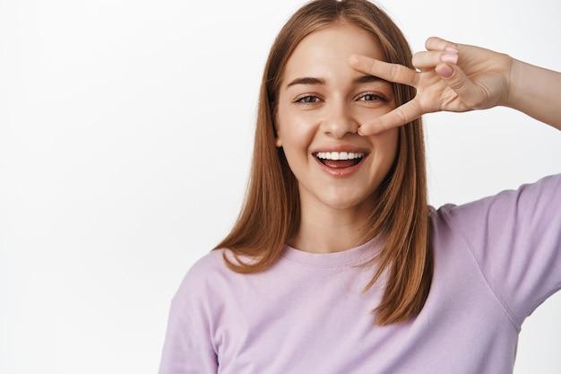 Portrait en gros plan d'une jeune femme naturelle, sourire candide d'une femme montrant le signe v de paix près de l'œil, concept de beauté de la femme et expressions du visage, mur blanc