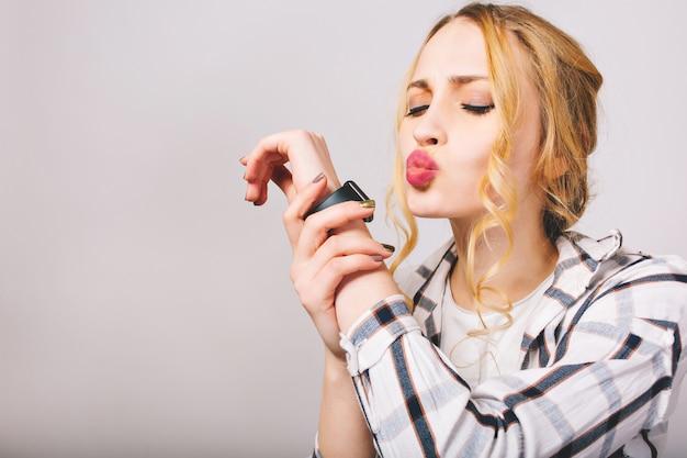 Portrait de gros plan de jeune femme séduisante avec maquillage de tous les jours tenant sa main avec montre-bracelet noire. curly jolie fille en chemise rayée posant les yeux fermés