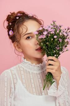 Portrait en gros plan d'une jeune femme sexy avec une peau propre et un bouquet de fleurs.