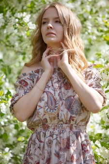 Portrait en gros plan d'une jeune fille blonde dans un jardin fleuri