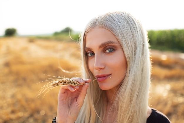 Portrait en gros plan d'une jeune fille blonde mignonne avec un épi de blé dans la bouche.