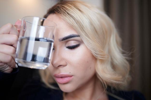 Portrait en gros plan d'une jeune fille avec un verre d'eau à la main qui se tient les yeux fermés comme un concept de maux de tête sévères et de malaise