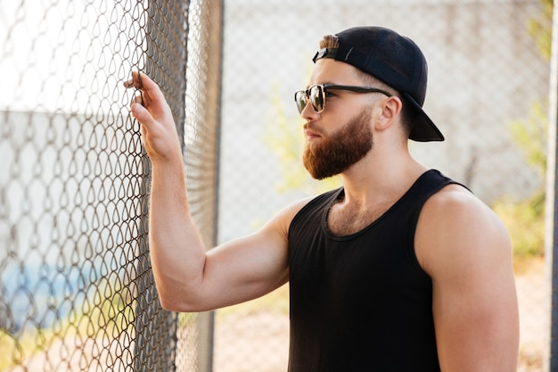 Portrait en gros plan d'un jeune homme barbu regardant à travers une clôture urbaine en métal portant des lunettes de soleil et une casquette à l'extérieur