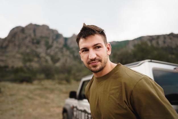 Portrait en gros plan d'un jeune homme debout près de la voiture dans la campagne
