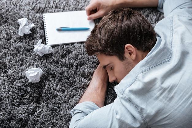 Portrait en gros plan d'un jeune homme épuisé dormant sur un tapis avec un bloc-notes