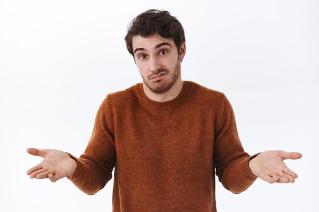 Portrait en gros plan d'un jeune homme incertain et indécis avec des poils, haussant les épaules, fait un visage confus, je ne sais pas pourquoi