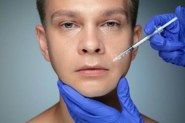 Portrait de gros plan de jeune homme isolé sur mur gris. procédure chirurgicale de remplissage, lèvres et pommettes. concept de la santé et de la beauté des hommes, de la cosmétologie, des soins du corps et de la peau. anti-âge.