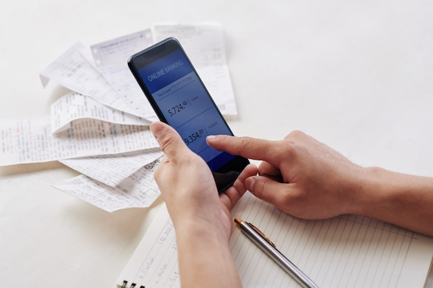 Portrait en gros plan d'un jeune homme utilisant une application bancaire sur un smartphone lors du paiement de factures pour un appartement ou une maison