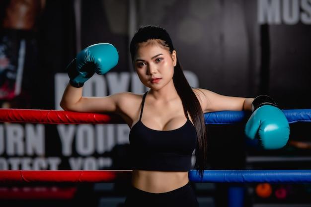 Portrait en gros plan jeune jolie femme en gant de boxe debout sur toile après entraînement avec fatigue, entraînement en salle de fitness,