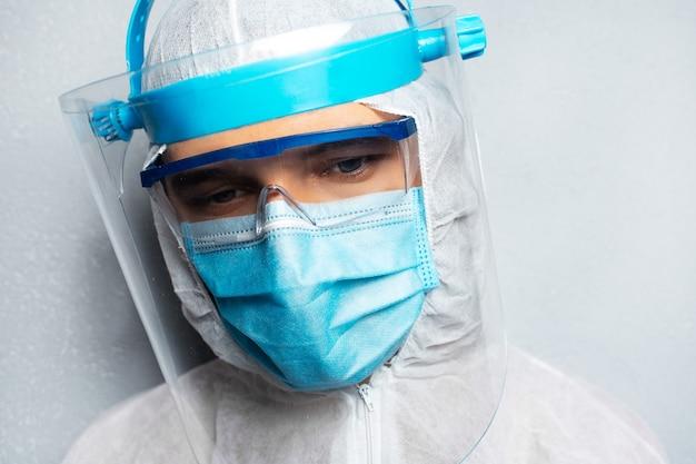 Portrait en gros plan d'un jeune médecin portant une combinaison epi contre le coronavirus et le covid-19.