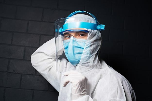 Portrait En Gros Plan D'un Jeune Médecin Portant Un Costume D'epi Contre Le Coronavirus Et Le Covid-19 Photo Premium
