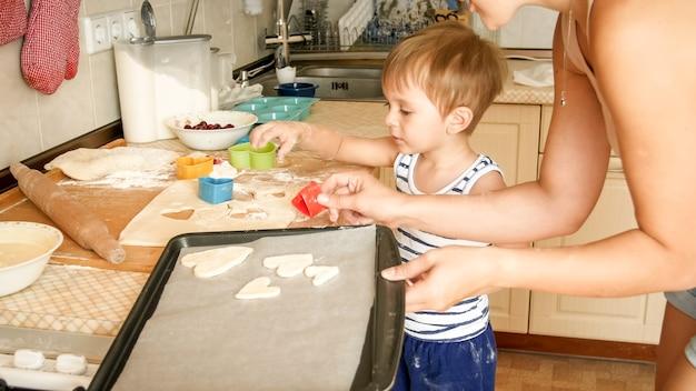 Portrait en gros plan d'une jeune mère avec un petit garçon tenant une plaque de cuisson et faisant des biscuits dans la cuisine