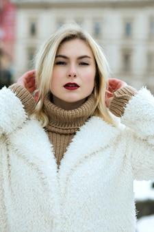 Portrait en gros plan d'un joli modèle aux lèvres rouges portant un manteau et une écharpe marchant dans la ville
