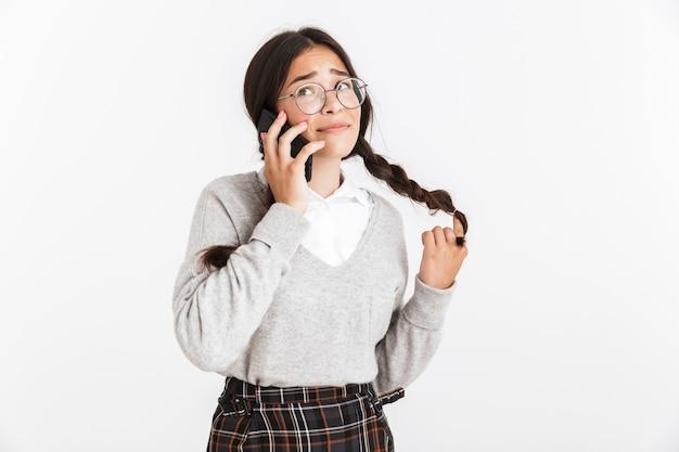 Portrait en gros plan d'une jolie adolescente portant des lunettes et un uniforme scolaire se réjouissant tout en parlant sur un smartphone isolé sur un mur blanc