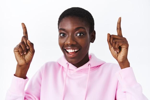 Portrait en gros plan d'une jolie femme afro-américaine impressionnée aux cheveux courts