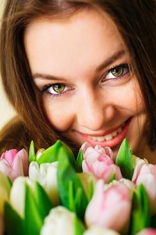 Portrait de gros plan de jolie femme avec des fleurs près de son visage. beauté naturelle. soin de la peau. bouquet de mariée de printemps. joyeuse journée de la femme