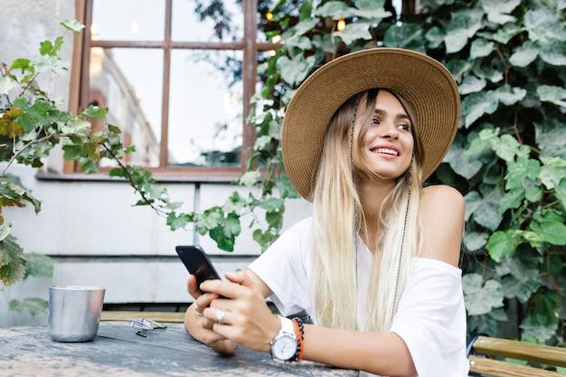 Portrait de gros plan de jolie fille aux cheveux longs au chapeau assis sur la terrasse. elle porte un t-shirt blanc aux épaules dénudées, style chapeau. elle sourit de côté et tient le téléphone