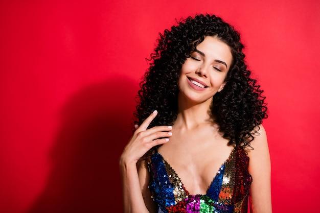 Portrait en gros plan d'une jolie fille aux cheveux ondulés gaie et rêveuse appréciant le jour de fête isolé sur fond de couleur rouge vif