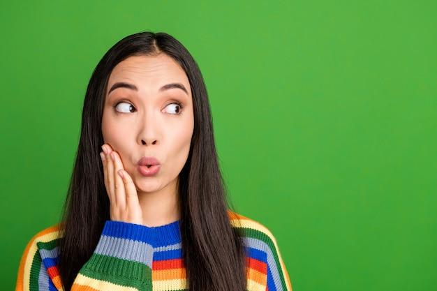 Portrait en gros plan d'une jolie fille étonnée regardant de côté copie espace vide vide lèvres moue isolées sur fond de couleur vert vif