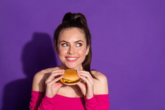 Portrait en gros plan d'une jolie fille gaie affamée mangeant un hamburger chaud en pensant à un espace de copie isolé sur un fond de couleur violet vif