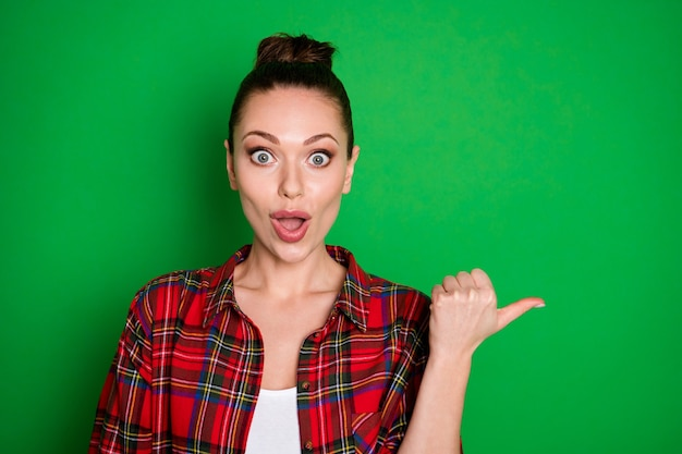 Portrait en gros plan d'une jolie fille gaie et gaie, jolie et étonnée, en chemise à carreaux, montrant une annonce publicitaire de bonne décision isolée sur un fond de couleur vert vif éclatant