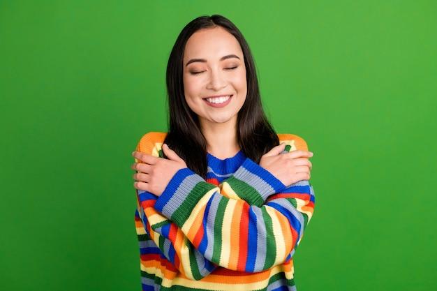 Portrait en gros plan d'une jolie fille gaie et rêveuse portant un pull chaud à rayures s'embrassant isolée sur fond de couleur vert vif