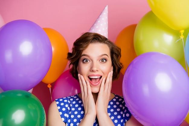 Portrait en gros plan d'une jolie fille joyeuse étonnée s'amusant parmi les boules d'air