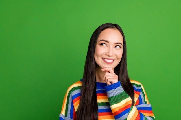 Portrait en gros plan d'une jolie fille joyeuse et pensive portant un pull rayé créant un espace de copie de solution isolé sur fond de couleur verte
