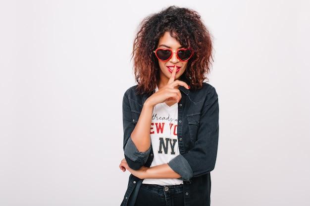 Portrait de gros plan de jolie fille avec une peau marron clair brillante isolée. photo intérieure d'une élégante jeune femme noire à lunettes de soleil porte des vêtements en denim à la mode.