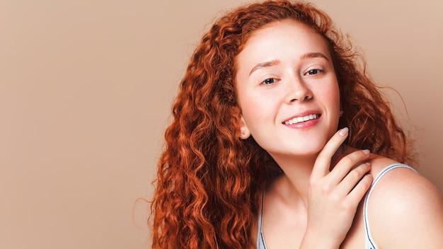 Portrait en gros plan d'une jolie fille souriante aux longs cheveux roux