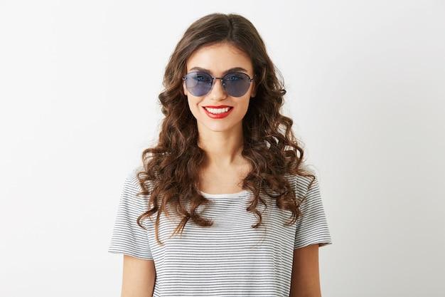 Portrait de gros plan de jolie jeune femme aux cheveux bouclés souriant isolé sur fond blanc portant des lunettes de soleil habillées en t-shirt