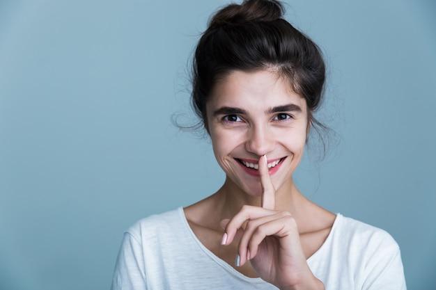 Portrait en gros plan d'une jolie jeune femme brune portant un t-shirt blanc isolé sur fond bleu, montrant un geste de silence