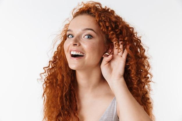 Portrait en gros plan d'une jolie jeune femme joyeuse avec de longs cheveux roux bouclés isolés, essayant d'entendre des rumeurs