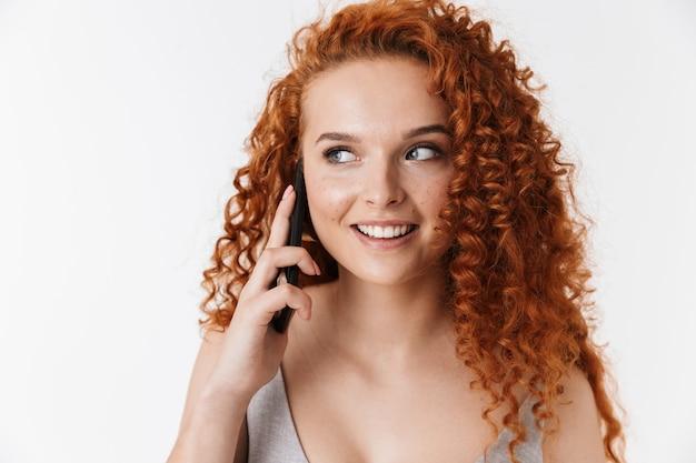 Portrait en gros plan d'une jolie jeune femme souriante aux longs cheveux roux bouclés isolés, parlant au téléphone portable