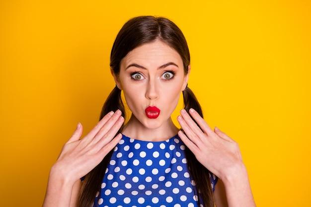 Portrait en gros plan d'une jolie jolie fille glamour étonnée de jeune fille portant des lèvres de moue chemisier en pointillé bleu grimaçant de bonnes nouvelles isolées sur un fond de couleur jaune vif éclatant