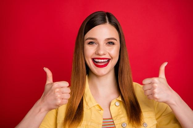 Portrait en gros plan d'une jolie jolie jolie jolie contente contente gaie joyeuse fille rousse montrant deux doubles pouces isolés sur fond de couleur rouge vif éclatant brillant