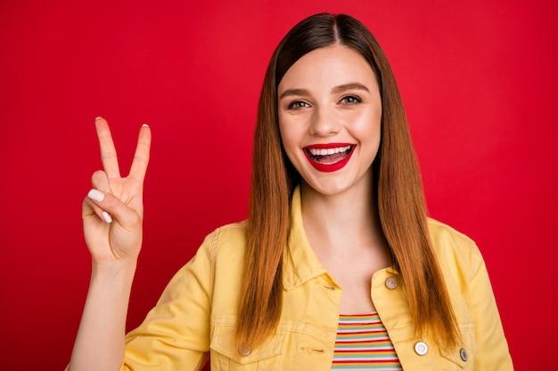 Portrait en gros plan d'une jolie jolie jolie jolie contente contente gaie joyeuse fille rousse montrant le signe v s'amusant isolé sur fond de couleur rouge vif brillant éclatant