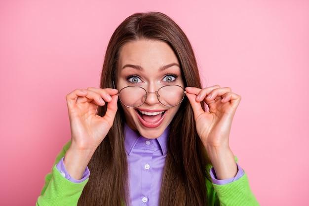 Portrait en gros plan d'une jolie jolie mignonne heureuse chanceuse gaie fille aux cheveux longs nerd geek touchant des spécifications isolées sur fond de couleur pastel rose
